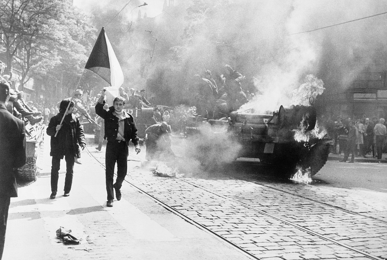 Photo of Czechoslovaks carry their national flag past a burning tank in Prague during the Soviet invasion of Czechoslovakia.